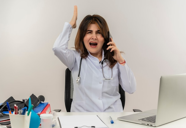 Verärgerte ärztin mittleren alters, die ein medizinisches gewand mit stethoskop trägt, das an der schreibtischarbeit am laptop mit medizinischen werkzeugen sitzt, spricht am telefon, das hand auf weißer wand mit kopienraum erhebt