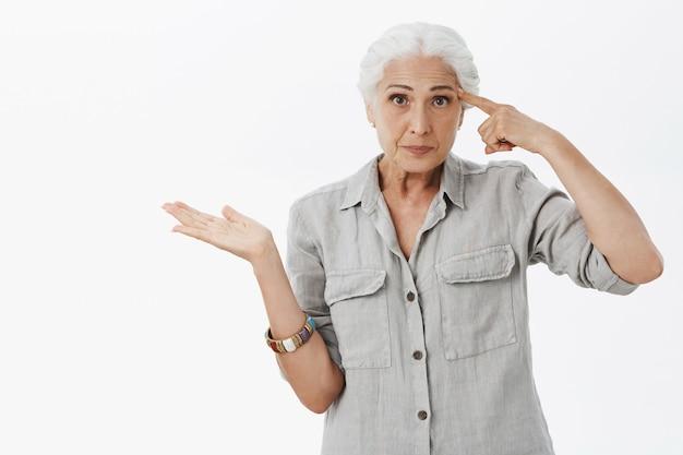 Verärgerte alte dame, die finger auf stirn zeigt, schimpfende person, die verrückt handelt
