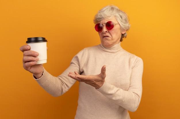 Verärgerte alte frau mit cremigem rollkragenpullover und sonnenbrille, die eine plastiktasse kaffee hält und mit der hand darauf zeigt