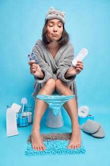Verärgerte asiatische frau mit dunklem haar hält damenbinde und schmerzmittel fühlt schmerzen während der menstruationsposen auf der toilettenschüssel in der toilette trägt eine schlafmaske, bequeme bademantelhöschen an den beinen isoliert auf blau