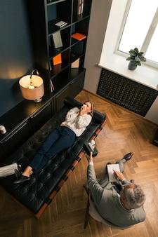 Verärgerte blonde kaukasische frau, die weint, während sie auf der couch in ihrem psychoanalytikerbüro liegt