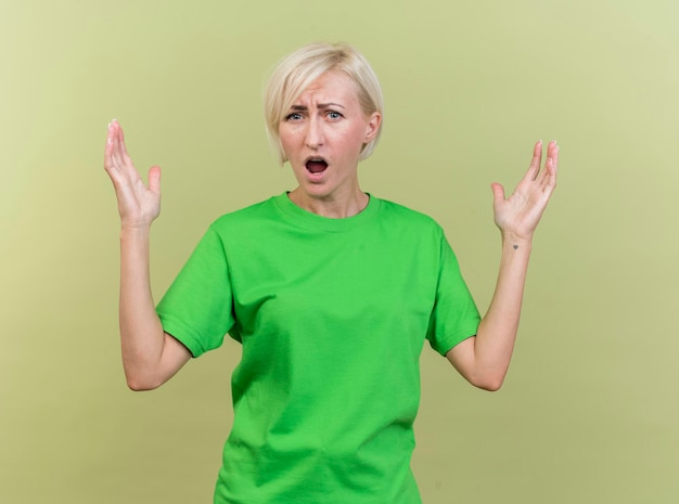 Verärgerte blonde slawische frau mittleren alters, die front betrachtet, die hände in der luft lokalisiert auf olivgrüner wand hält
