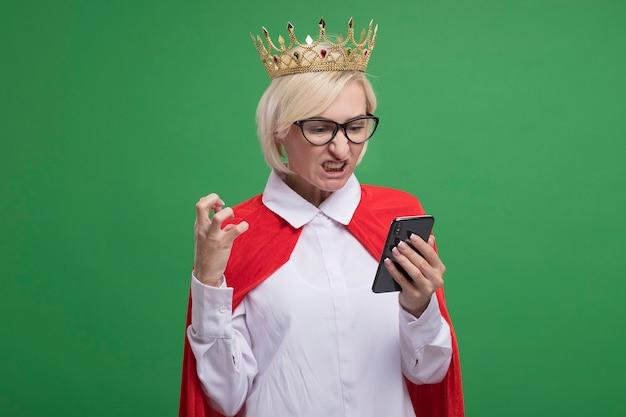 Verärgerte blonde superheldin mittleren alters in rotem umhang mit brille und krone, die das handy hält und betrachtet, das die hand in der luft hält, isoliert auf grüner wand mit kopierraum