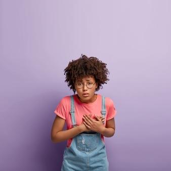 Verärgerte depressive junge frau mit einem afro, der in overalls posiert