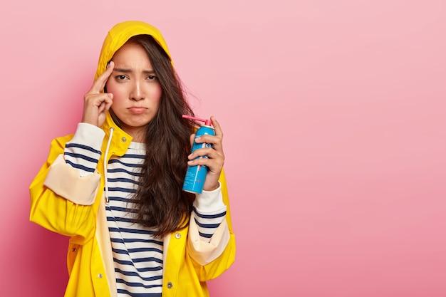 Verärgerte düstere frau mit asain-aussehen, leidet unter kopfschmerzen, ist im herbst krank, verwendet spray zur heilung von halsschmerzen, berührt die schläfe mit dem zeigefinger