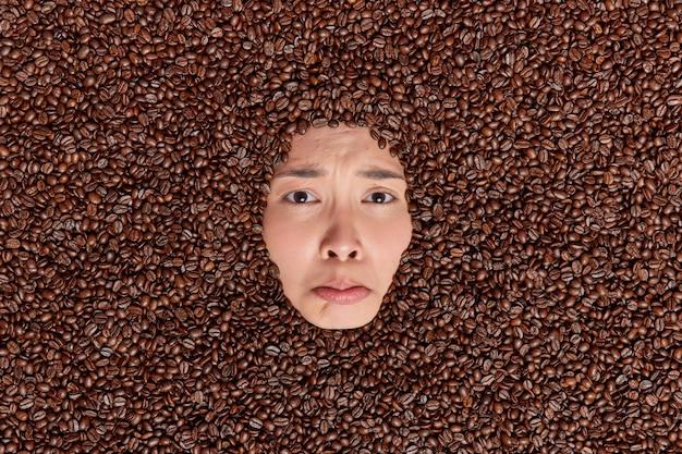Verärgerte düstere frau zeigt nur ihr gesicht durch kaffeebohnen