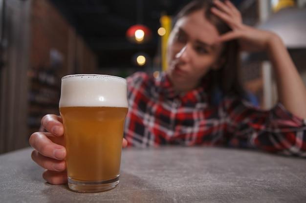 Verärgerte einsame frau, die bierglas hält und an der kneipe trinkt