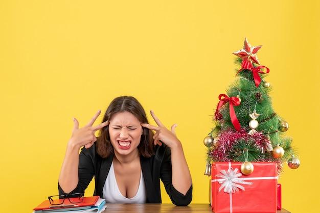 Verärgerte emotionale und nervöse junge frau, die an einem tisch nahe geschmücktem weihnachtsbaum im büro auf gelb sitzt