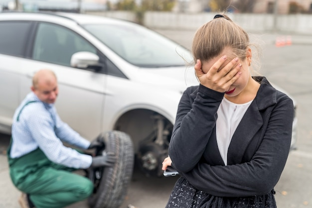 Verärgerte frau auf autoservice mit kaputtem auto