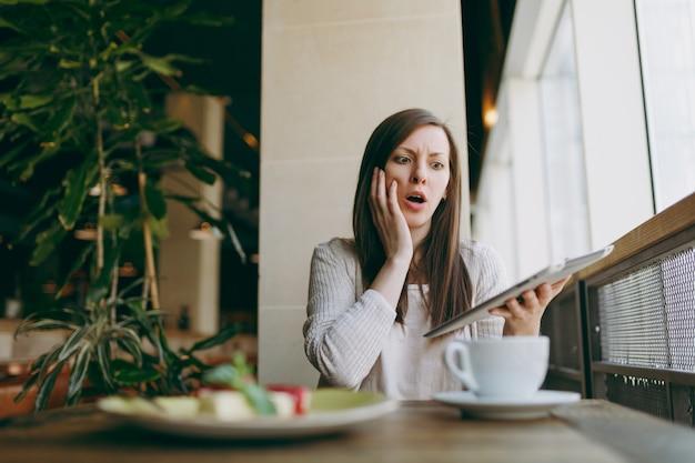 Verärgerte frau, die allein in der nähe eines großen fensters im café mit einer tasse cappuccino, kuchen sitzt und sich in der freizeit entspannt. weibliche arbeit, schlechte nachrichten auf pc-tablet-computer-rest im café lesen. lifestyle-konzept