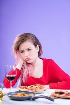 Verärgerte frau, die am tisch mit einem glas rotwein und pizza sitzt
