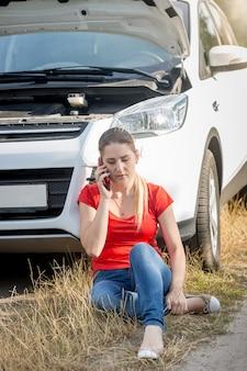 Verärgerte frau, die auf dem boden sitzt und sich auf ein kaputtes auto stützt