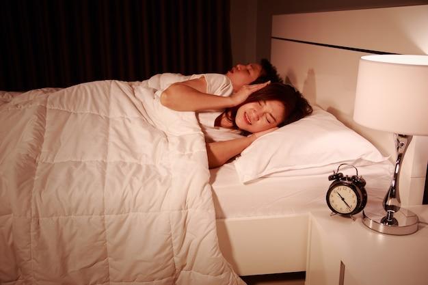 Verärgerte frau, die ihre ohren vom geräusch des ehemanns blockiert, der nachts schnarcht