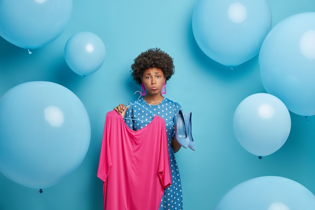 Verärgerte frau hat ein problem damit, was sie anziehen soll, hält rosa kleid auf kleiderbügel und blaue schuhe mit hohen absätzen, traurige kleidungsstücke passen nicht zusammen, wählt outfit für besondere anlässe, drückt negative emotionen aus