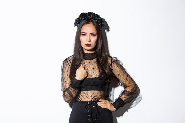 Verärgerte frau im hexenkostüm, die auf sich selbst zeigt, verärgert die stirn runzelt, frustriert im halloween-kostüm steht und über weißem hintergrund steht.