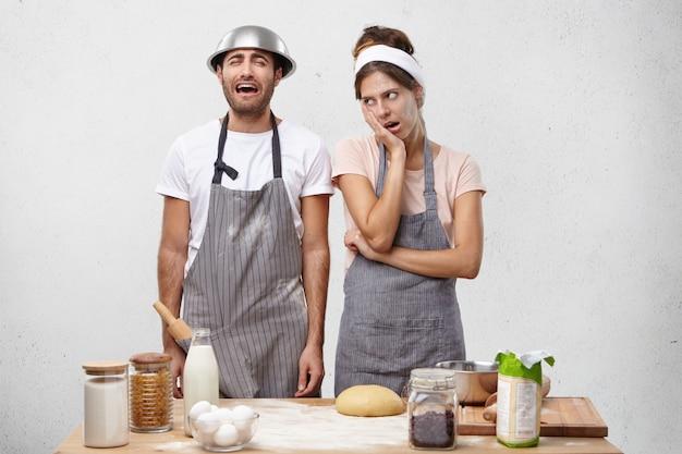 Verärgerte frau in der schürze, die mit ehemann gereizt wird, der in der küche jammert