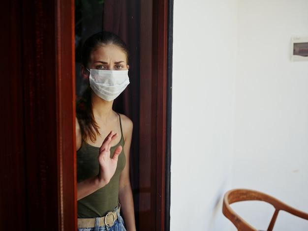 Verärgerte frau in medizinischer maske, die aus der fenstersperre schaut