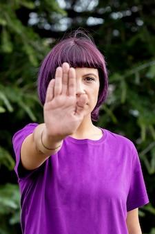 Verärgerte frau mit im purpur die handpalme zeigend, die stopp sagt