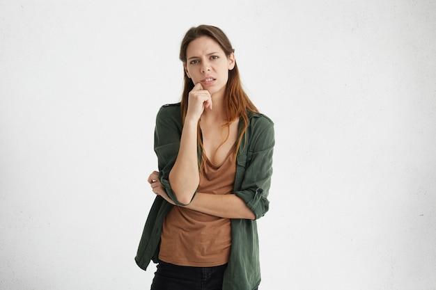 Verärgerte frau mit schönem aussehen, die lässiges braunes t-shirt und grüne jacke trägt, die ihre hand auf kinn hält, das müden und unglücklichen blick hat.