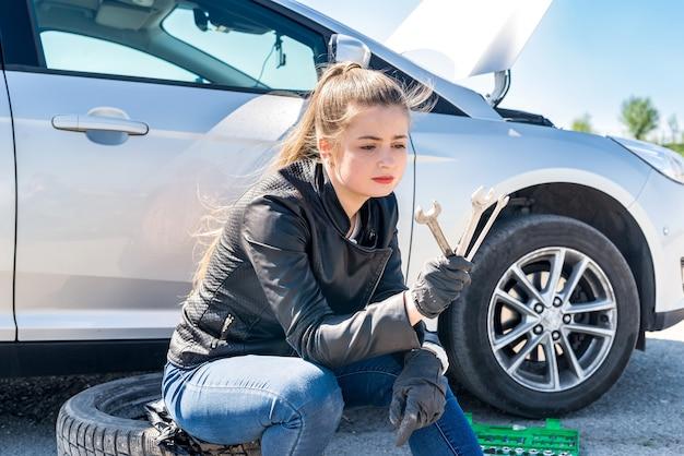 Verärgerte frau mit verschiedenen schraubenschlüsseln und kaputtem auto