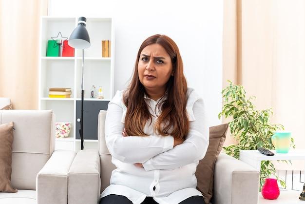 Verärgerte frau mittleren alters in weißem hemd und schwarzer hose, die mit stirnrunzelndem gesicht auf dem stuhl im hellen wohnzimmer sitzt