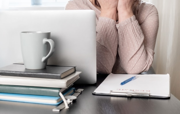 Verärgerte frau schloss ihr gesicht der hände in der nähe ihres arbeitsplatzes mit laptop und lebenslauf anwendung.