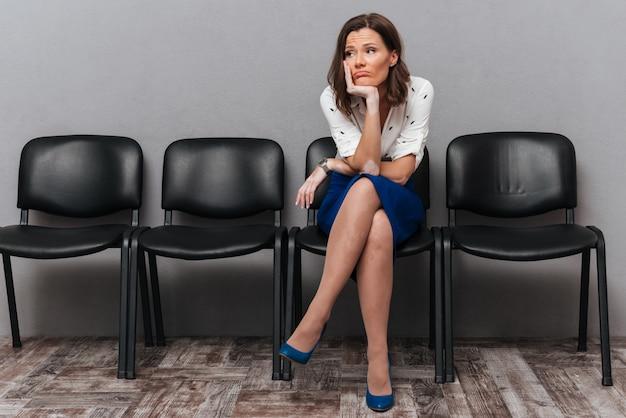 Verärgerte geschäftsfrau, die auf stühlen wartet