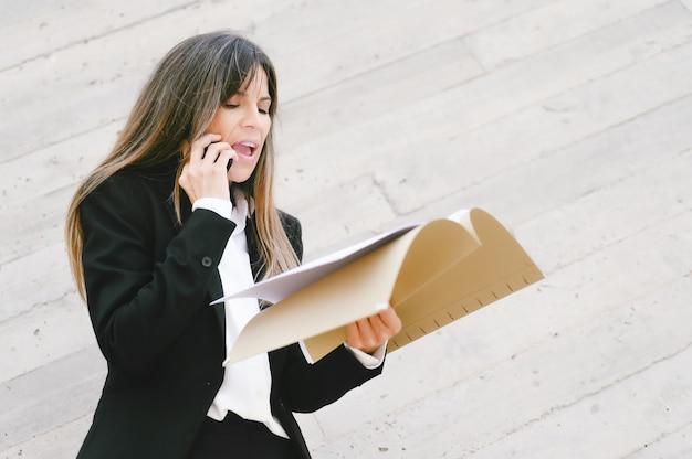 Verärgerte geschäftsfrau, die dokumente hält und am telefon schreit