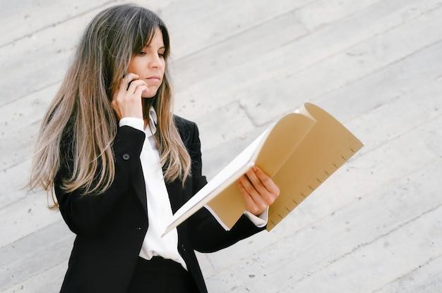 Verärgerte geschäftsfrau, die dokumente hält und am telefon spricht