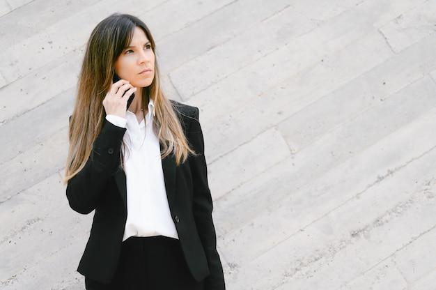 Verärgerte geschäftsfrau, die draußen am telefon spricht