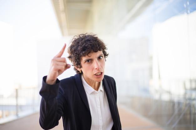Verärgerte geschäftsfrau, die mit dem finger zeigt