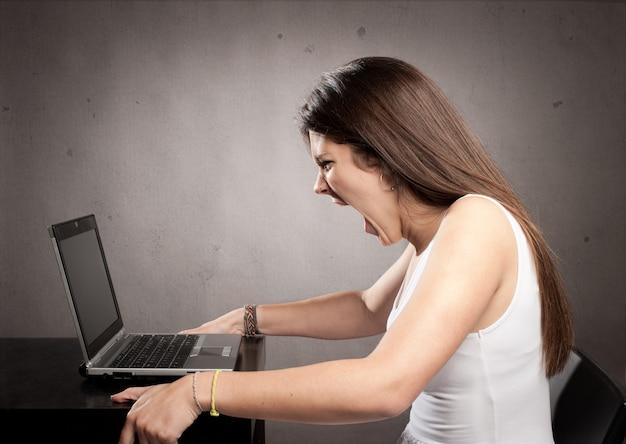 Verärgerte geschäftsfrau, die mit einem laptop arbeitet