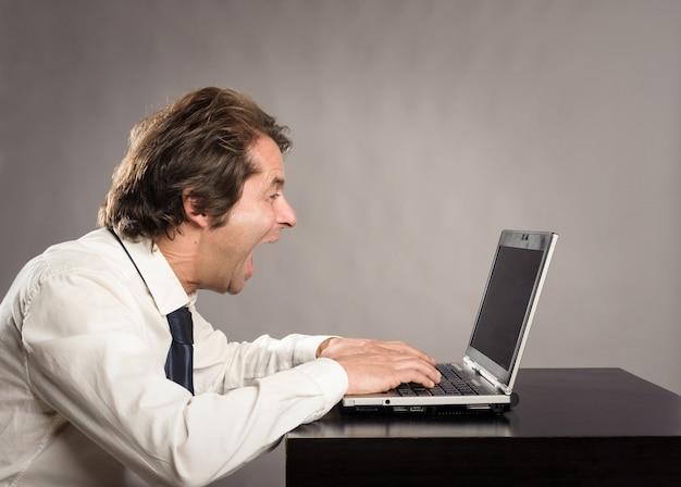 Verärgerte geschäftsfrau, die mit einem laptop im büro arbeitet