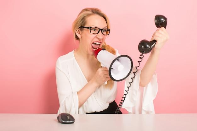 Verärgerte geschäftsfrau mit telefon und lautsprecher
