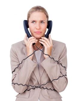 Verärgerte geschäftsfrau verwirrt in den telefondrähten