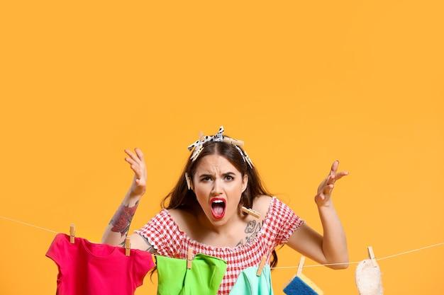 Verärgerte hausfrau mit wäsche auf farbhintergrund