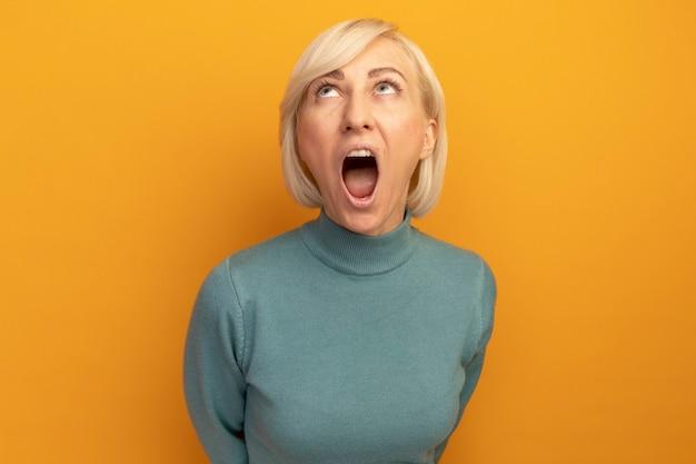 Verärgerte hübsche blonde slawische frau schaut isoliert auf orange wand auf