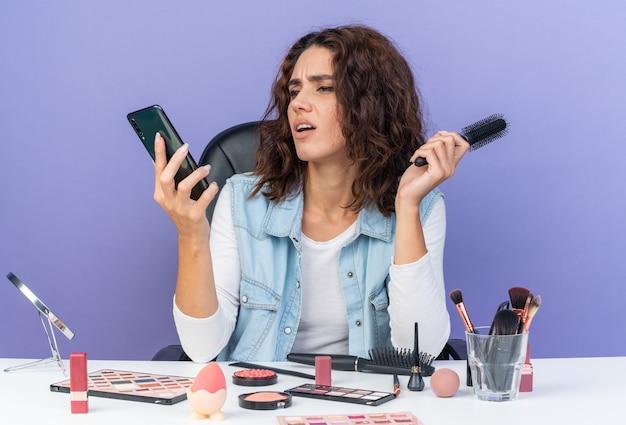 Verärgerte hübsche kaukasische frau, die am tisch mit make-up-tools sitzt und kamm hält und auf das telefon isoliert auf lila wand mit kopienraum schaut