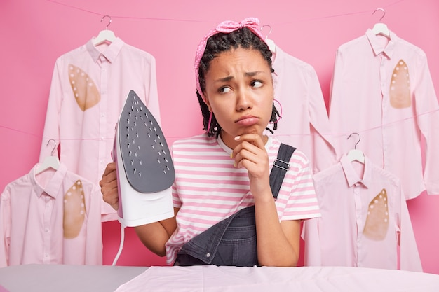 Verärgerte junge afroamerikanische haushälterin mit dreadlocks sieht leider weg, will keine kleidung bügeln hält elektrisches bügeleisen trägt stirnband gestreiftes t-shirt und overalls, die der hausarbeit müde sind.