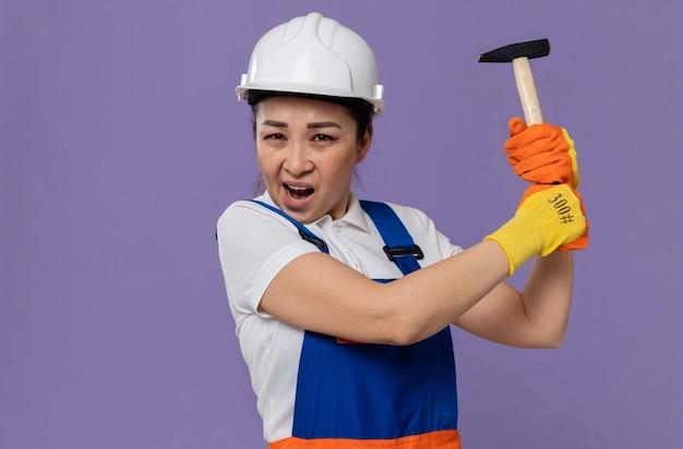 Verärgerte junge asiatische baumeisterin mit weißem schutzhelm und handschuhen mit hammer
