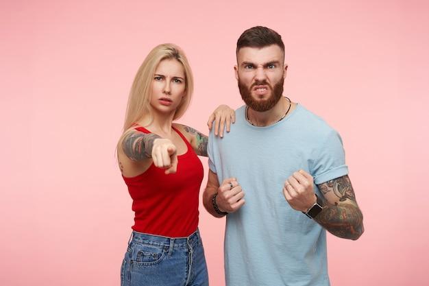 Verärgerte junge attraktive blonde frau, die mit dem zeigefinger nach vorne zeigt, während sie mit ihrem verrückten braunhaarigen, tätowierten, gutaussehenden freund über rosa hintergrund posiert