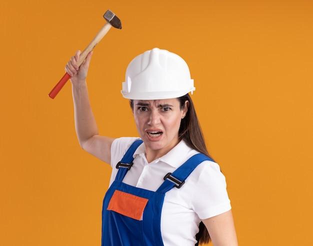 Verärgerte junge baumeisterin in uniform, die hammer auf orange wand lokalisiert hält