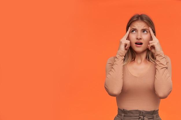 Verärgerte junge blauäugige kurzhaarige blonde dame mit lässiger frisur, die erhobene hände an den schläfen hält und verwirrt nach oben schaut, isoliert über der orangefarbenen wand