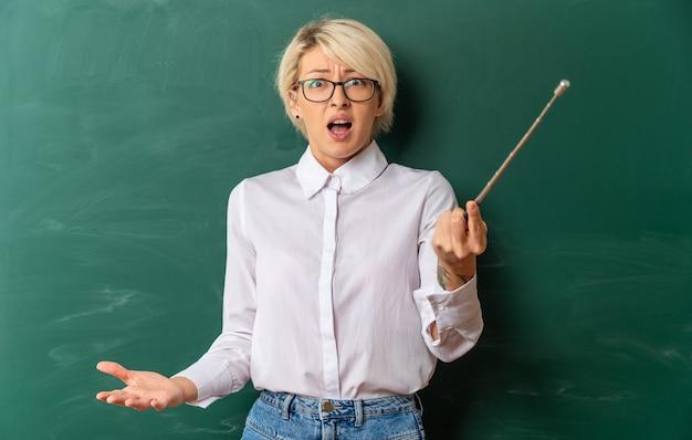Verärgerte junge blonde lehrerin mit brille im klassenzimmer, die vor der tafel steht und einen zeiger hält, der nach vorne schaut und leere hand zeigt