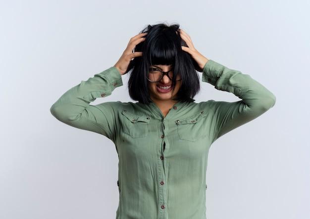 Verärgerte junge brünette kaukasische frau in optischen gläsern hält kopf, der kamera lokalisiert auf grünem hintergrund mit kopienraum hält