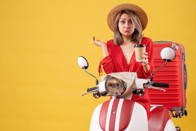 Verärgerte junge dame im roten kleid mit kaffeetasse in der nähe von moped