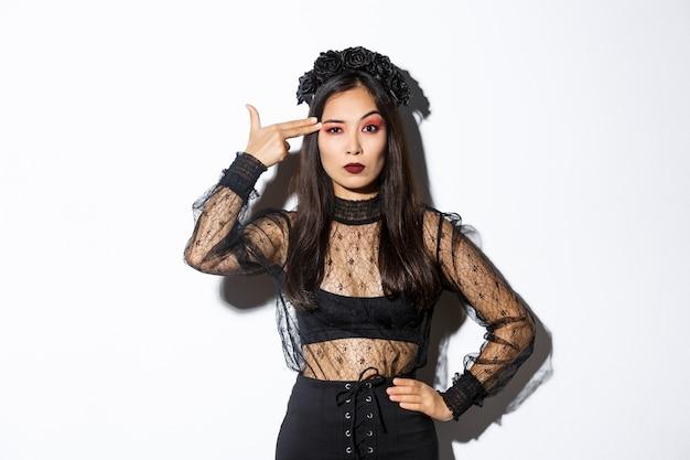 Verärgerte junge frau, die enttäuscht aussieht, während sie fingerpistolengeste über kopf macht, halloween-kostüm tragend, über weißem hintergrund stehend.