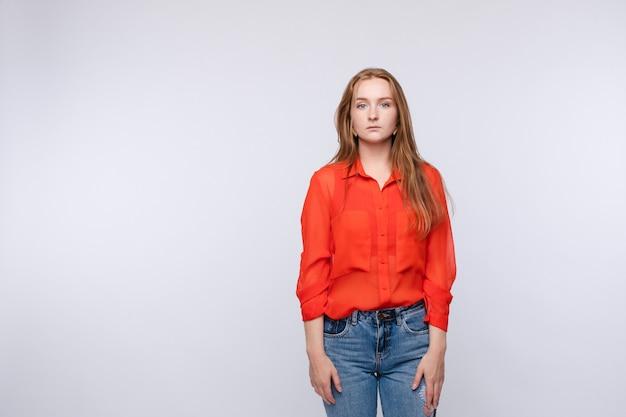Verärgerte junge frau, die rote bluse und jeans trägt