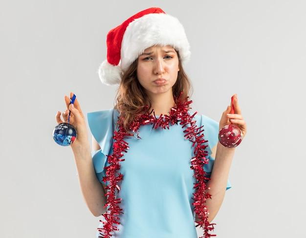 Verärgerte junge frau im blauen oberteil und im weihnachtsmannhut mit lametta um ihren hals, der weihnachtskugeln hält, die mit traurigem ausdruck schauen