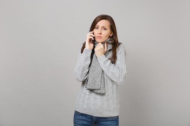 Verärgerte junge frau im grauen pullover, schal, die auf dem handy spricht lokalisiert auf grauem wandhintergrund im studio. gesunde mode-lifestyle-leute aufrichtige emotionen, konzept der kalten jahreszeit. kopieren sie platz.